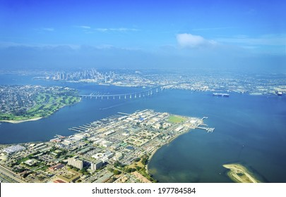 Aerial view of the Coronado island and bridge in the San Diego Bay in Southern California. A view of the Skyline of the city and some boats crossing the the sea.