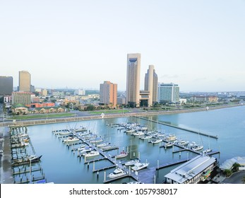 Aerial view Corpus Christi bay front skyline and yacht parking area in morning. City harbor bridge with row of oil tanks far right in distance. A South Texas city on Gulf of Mexico, vacation getaway