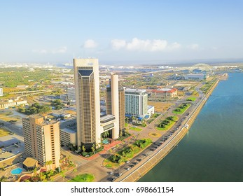 Aerial view of Corpus Christi skylines along  North Bayfront Park at sunrise. City harbor bridge with row of oil tanks at far right in distance. A South Texas city on Gulf of Mexico, vacation getaway