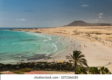 Aerial view of Corralejo Beach and its dunes crowded with tourists in Fuerteventura, Spain.