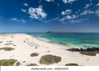 Aerial view of Corralejo beach and dunes with turquoise water in Fuerteventura, Spain with Isla de Lobos and Lanzarote in the background.