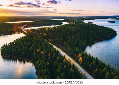Aerial view of country road in green summer forest with blue lakes at sunset in Finland