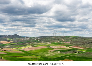 Aerial view of the countryside outside Medinaceli in Soria, Spain, with a wind farm in the background.