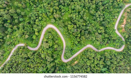 Aerial view of countryside road passing through the green forrest and mountain