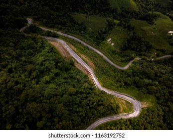 Aerial view of countryside road passing through the lush greenery and foliage tropical rain forest mountain landscape in the Northern Thailand