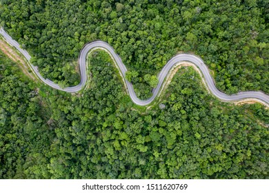Aerial view of countryside road passing through the green forrest and mountain.