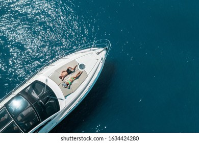 aerial view of couple enjoying sunbathing on the luxury yacht moving in the sea. Travel vacation
