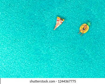 Aerial view of couple floating on inflatable pizza and pineapple shaped mattresses, relaxing on transparent sea.