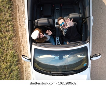 aerial view couple saying goodbye before driving away in cabriolet car