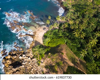 Aerial view of cozy white sand beach with turquoise clear sea water. Sri Lanka beach view from the air, Mirissa