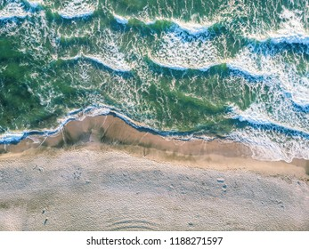 Aerial view of crashing wave in ocean with warm sunset light. Wave crashing on reef. Top view