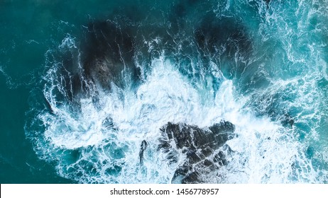 Aerial view of crashing waves on rocks. Aerial view of sea waves and fantastic Rocky coast,Background texture of a rocky shore and blue and turquoise water and waves of the Atlantic Ocean New Zealand.