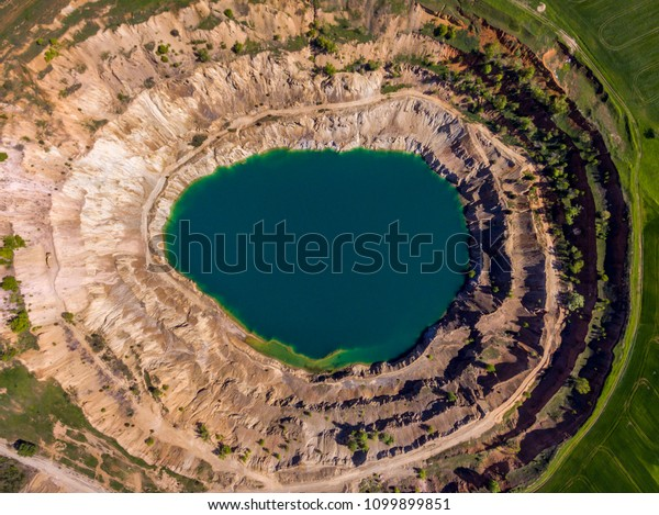 Aerial view of a crater created by mining machines and filled up with water creating an artificial lake.