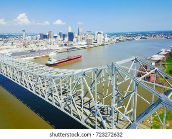 Aerial view of Crescent City Connection and riverside Downtown New Orleans again cloud blue sky. Overhead view the cantilever bridges, cruise ship, cargo ship, container terminal on Mississippi river.