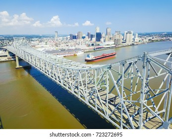 Aerial view of Crescent City Connection and riverside Downtown New Orleans again cloud blue sky. Overhead view the cantilever bridges and an empty cargo container ship on Mississippi river.