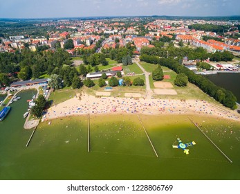Aerial view of crowded sandy beach during hot summer day on Niegocin Lake in Gizycko town, Mazury, Poland