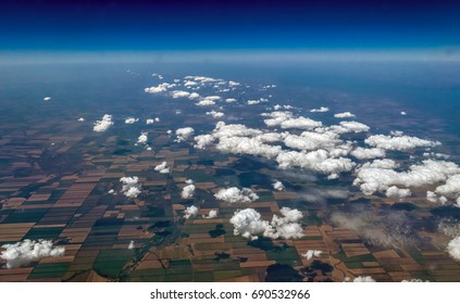 Aerial view of curly sunny clouds and their shadows on mosaic landscape