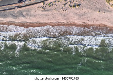 Aerial view of cyan-green sea waves crashing on sandy shore in Barmouth, North Wales, UK