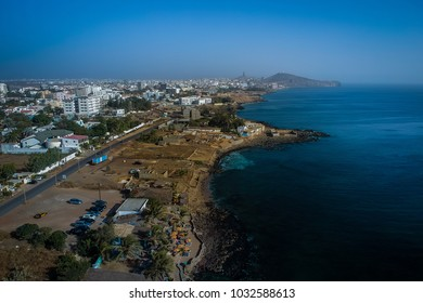 Aerial view of Dakar, looking from Ngor towards the African Renaissance Monument which is seen in the far background. Beach and a bar is seen in the front.