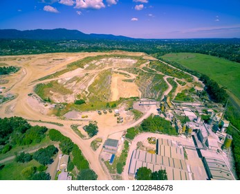 Aerial view of decommissioned mine site with old structures and heavy machinery