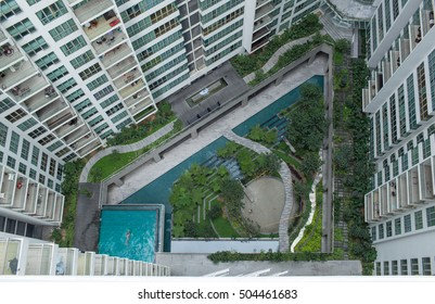 Aerial view of decorative green garden with people, water scene and swimming pool in residential area