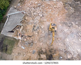 aerial view of demolition site with ruined old building and yellow excavator clearing out redevelopment area
