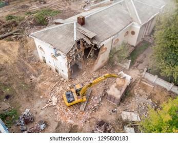 aerial view of demolition site with ruins and debris. destruction of old building. excavator loading dumper truck with debris