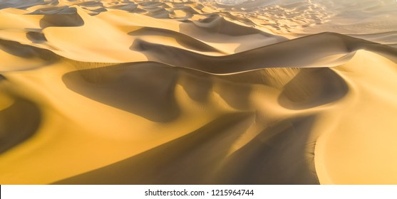 aerial view of desert landscape in sunset, panoramic view of golden sand dunes rolling