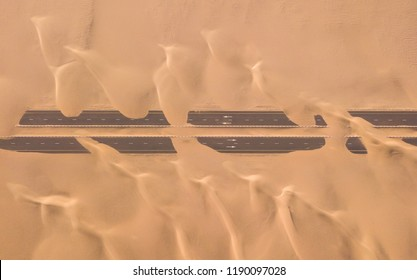 Aerial view of a desert road being run over by sand dunes photographed from a drone at sunrise. Dubai, UAE.