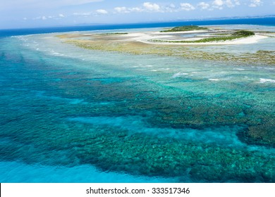 Aerial view of a deserted tropical island and coral reef lagoon of an atoll, Okinawa, Japan
