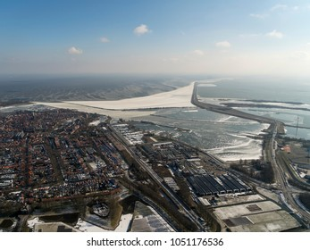 Aerial view of the dike between the city Enkhuizen and Lelystad. It divides lake Markermeer and IJsselmeer. It is a winter shot with a large snowfield at the north side of the dike and a clear horizon