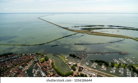 Aerial view of the dike to Lelystad, Flevoland, as seen from the city and harbour of Enkhuizen in The Netherlands. The highway divides lake IJsselmeer and Markermeer. It is a beautiful clear day.