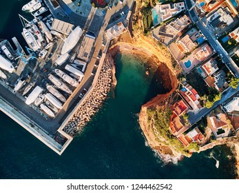 Aerial view directly from above, moored vessels at Port Adriano, located just below the cliffs of the small neighborhood of El Toro villas with swimming pools. Island of or Mallorca or Majorca Spain