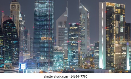 Aerial view to downtown and financial district in Dubai night timelapse, United Arab Emirates with illuminated skyscrapers and highways.