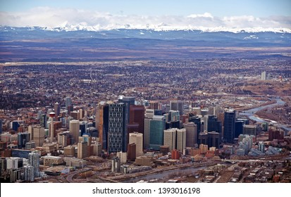 An aerial view of downtown financial and oil and gas corporate hub in the city of Calgary with snow covered canadian rockies in the background