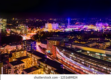 Aerial view of downtown Hamburg, Germany,  and the famous funfair (German: Hamburger Dom), illuminated at night.