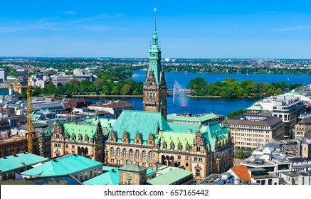Aerial view of downtown Hamburg, Germany, on a sunny day. The city hall (Rathaus) is the most prominent building with the lake Alster in the background.