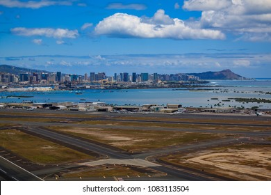 Aerial view of downtown Honolulu, Diamond Head and the runway of Daniel K. Inouye International Airport (HNL), formerly known as Honolulu International Airport in Hawaii from a helicopter