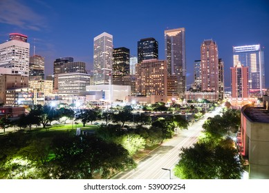 Aerial view downtown Houston illuminated at blue hour with green city park and modern skylines light. The most populous city in Texas, fourth-most in United States. Architecture and travel background.