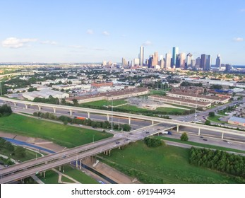 Aerial view downtown and interstate 10 highway (Katy freeway). Suburbs area, factory/warehouse, stack interchange and elevated road junction overpass at sunset from northwest side of Houston, Texas,US