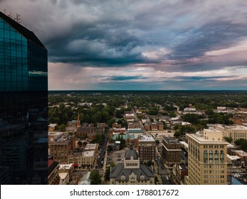 Aerial View of downtown Lexington, Kentucky, Bluegrass Region USA during dramatic clouds sunset. Reflective blue windows office building partially visible on the left side.