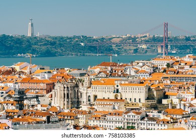 Aerial View Of Downtown Lisbon Skyline Of The Old Historical City And Cristo Rei Santuario (Sanctuary Of Christ the King Statue) In Portugal