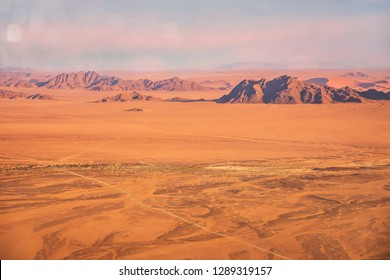 Aerial view of the dramatic landscape of the Namib Desert, showing long straight roads running through flat, empty, desolate terrain. In Sossusvlei, Namibia.