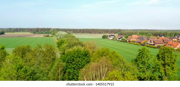 Aerial view of the drone ascent over the tops of the trees with a view of a field and the edge of a village with residential houses.