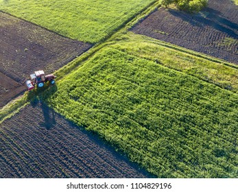 Aerial view from the drone, a bird's eye view of agricultural fields with a road through and a tractor on it, in the evening, at sunset