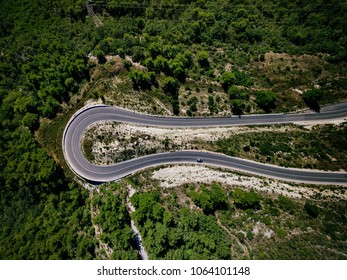 Aerial view from drone of curve road with a car on the mountain with green forest in Croatia