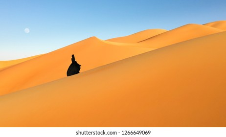 Aerial view from a drone flying next to a woman in abaya (United Arab Emirates traditional dress) walking on the dunes in the desert of the Empty Quarter. Abu Dhabi, UAE.