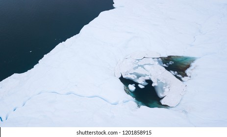 Aerial view from a drone flying over a frozen glacier with a small melt water lake on top. Disko bay, Greenland.
