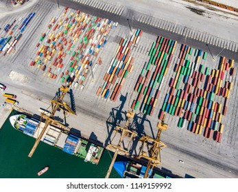 Aerial view from drone of a freighter getting loaded and containers in a port. Thessaloniki city, Greece - August 4, 2018