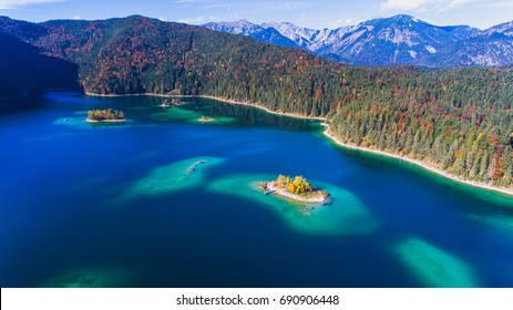 Aerial view from a drone of the German lake situated in Garmisch Partenkirchen, in Bavarian area. Eibsee from top with a small island and forest in the background. Colorful landscape in a rural spot.